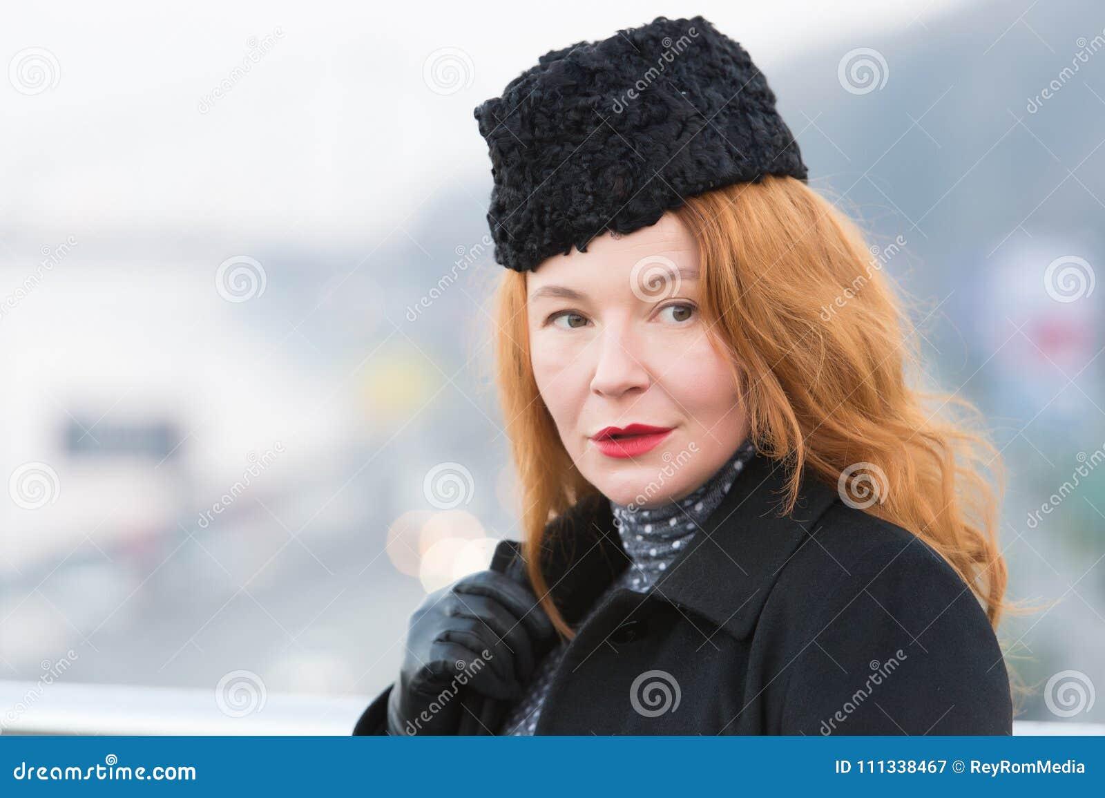 Портрет женщин в черных пальто и черной шляпе Крупный план женщин румян с красными губами Красивая дама в пальто на предпосылке г
