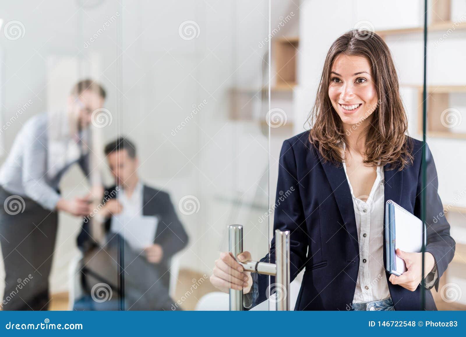 Портрет жизнерадостного современного женского профессионала в современном офисе