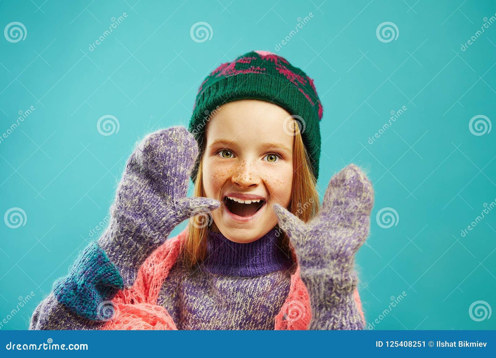 Портрет жизнерадостной девушки ребенка носит mittens зимы, теплый свитер, шляпу с pompom и openwork шарф накидки на сини