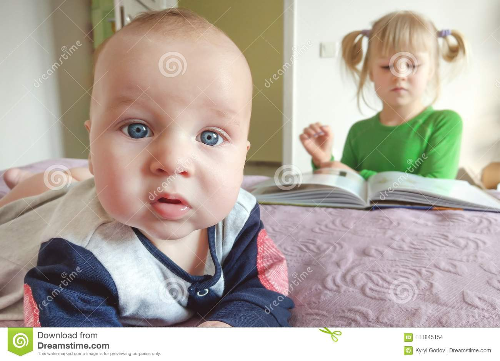 Портрет задумчивого маленького младенческого мальчика делая selfie на кровати Книга чтения сестры на предпосылке Различные интере