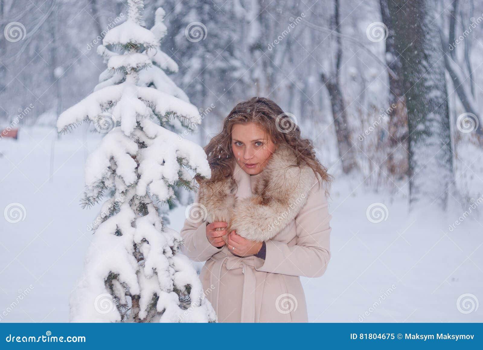 Портрет зимы женщины в белом пальто во время снежностей в парке
