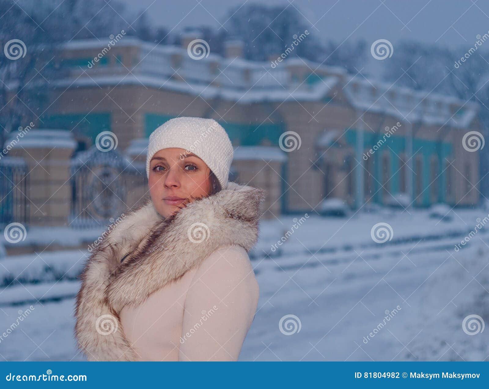 Портрет зимы женщины в белых пальто и шляпе во время снежностей в парке