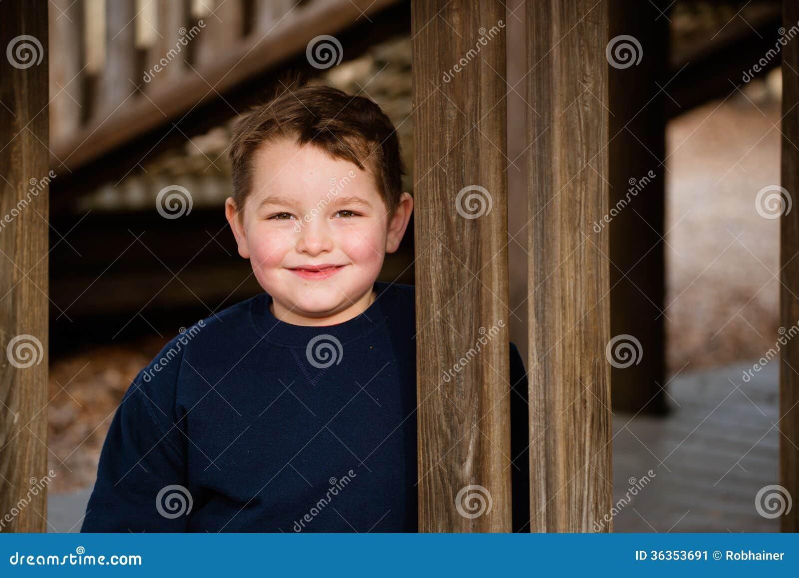 Портрет зимы счастливого мальчика на спортивной площадке