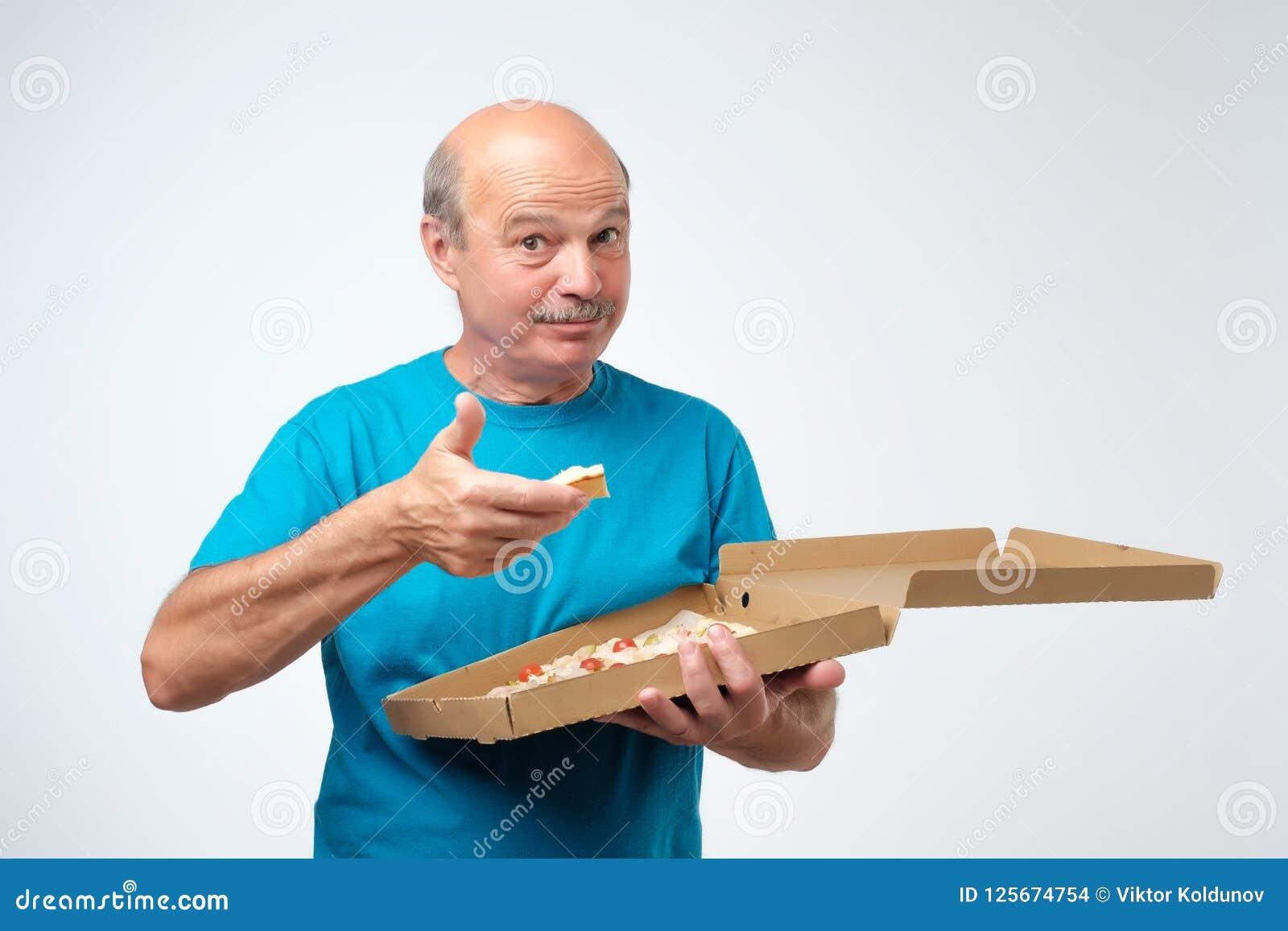 Портрет зрелого европейского человека есть кусок пиццы В его руках он держит коробку еды Всход студии