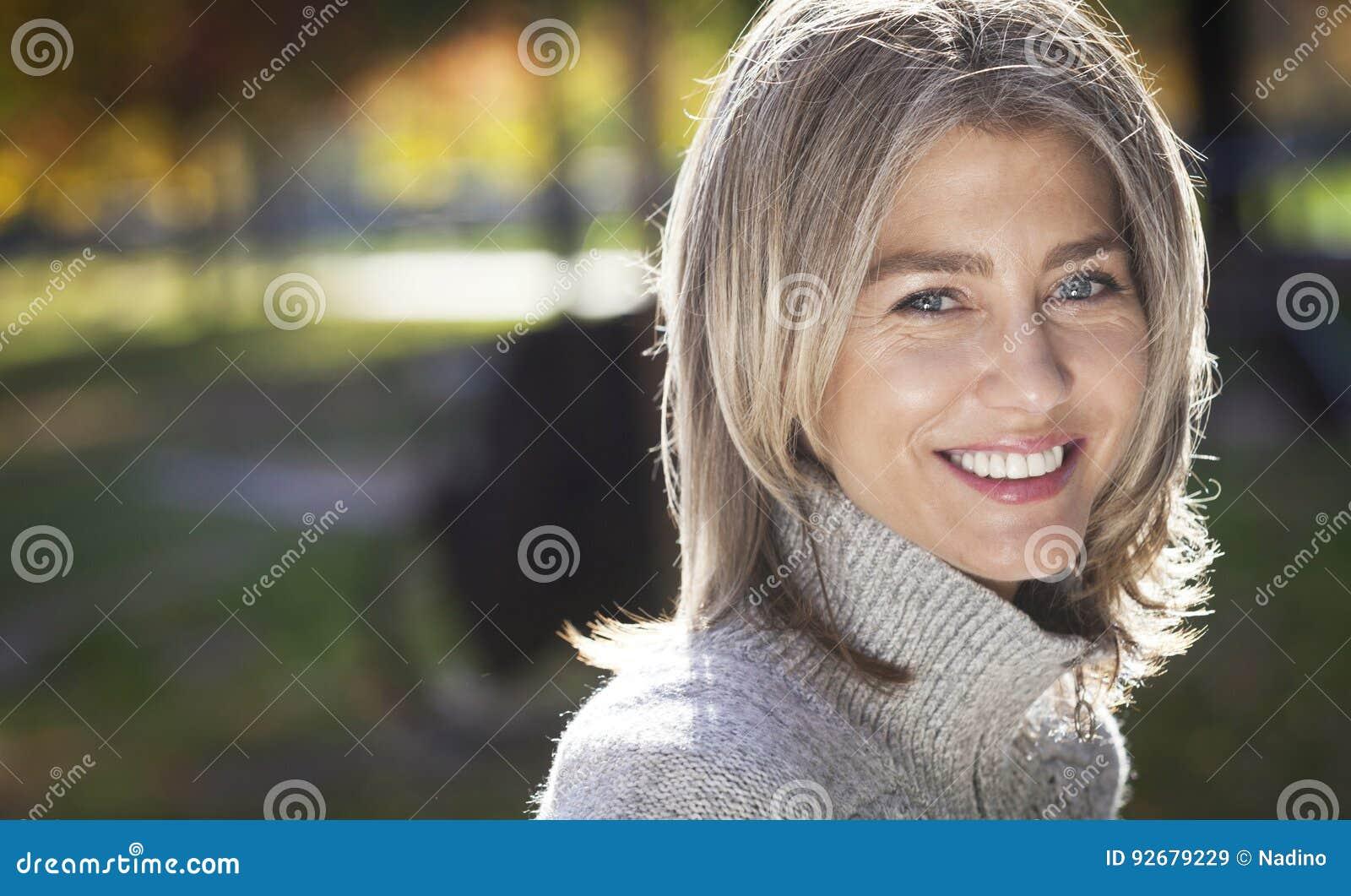 Портрет зрелой женщины усмехаясь на камере Серые волосы