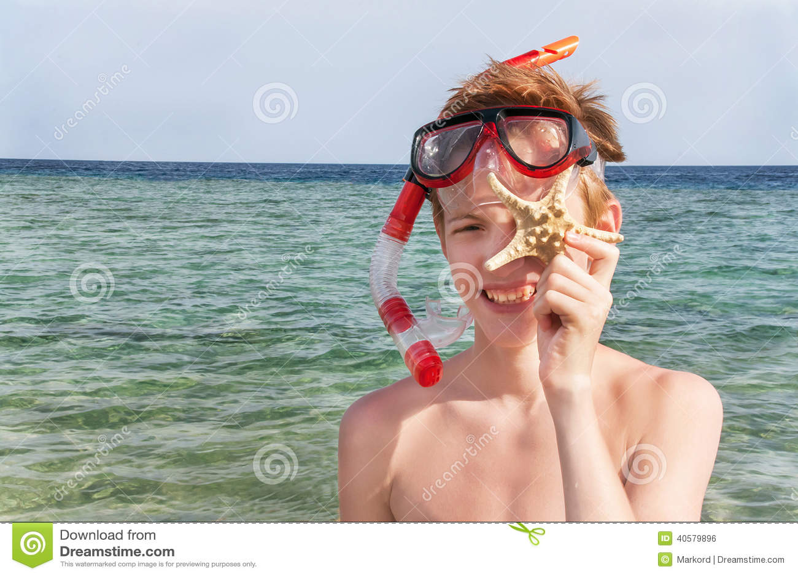 Портрет кавказского мальчика на пляже с snorkeling маской и