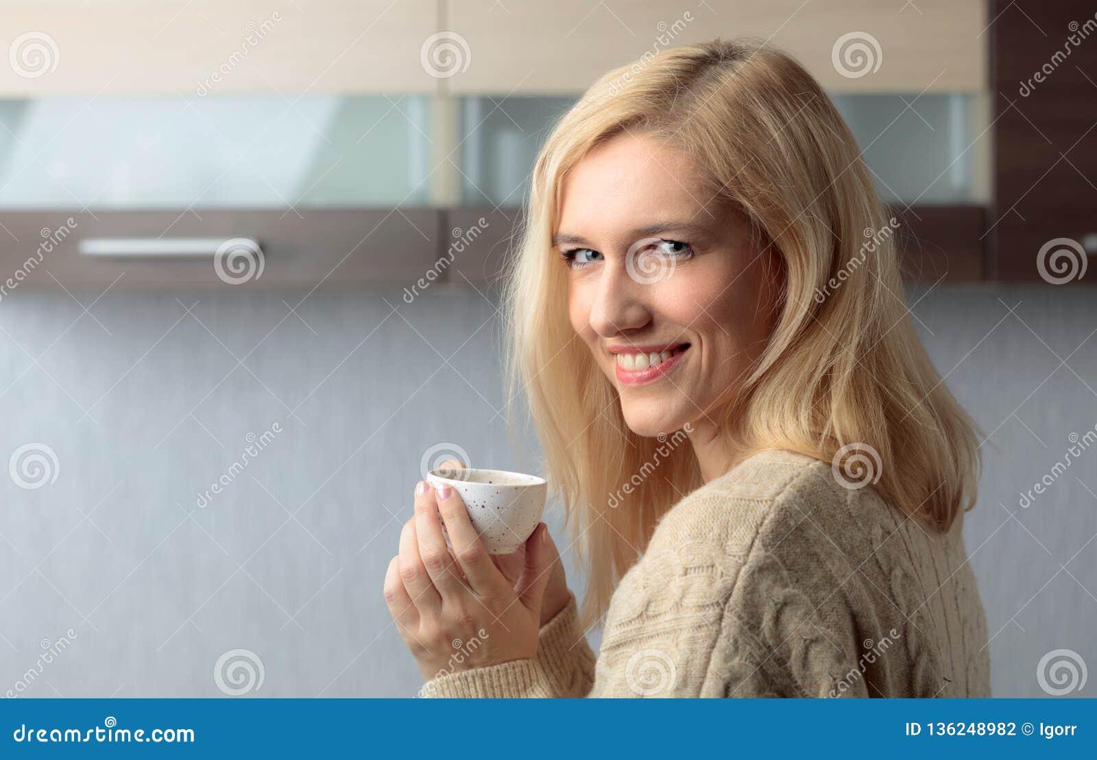 Портрет конца-вверх красивой средней женщины возраста с чашкой кофе