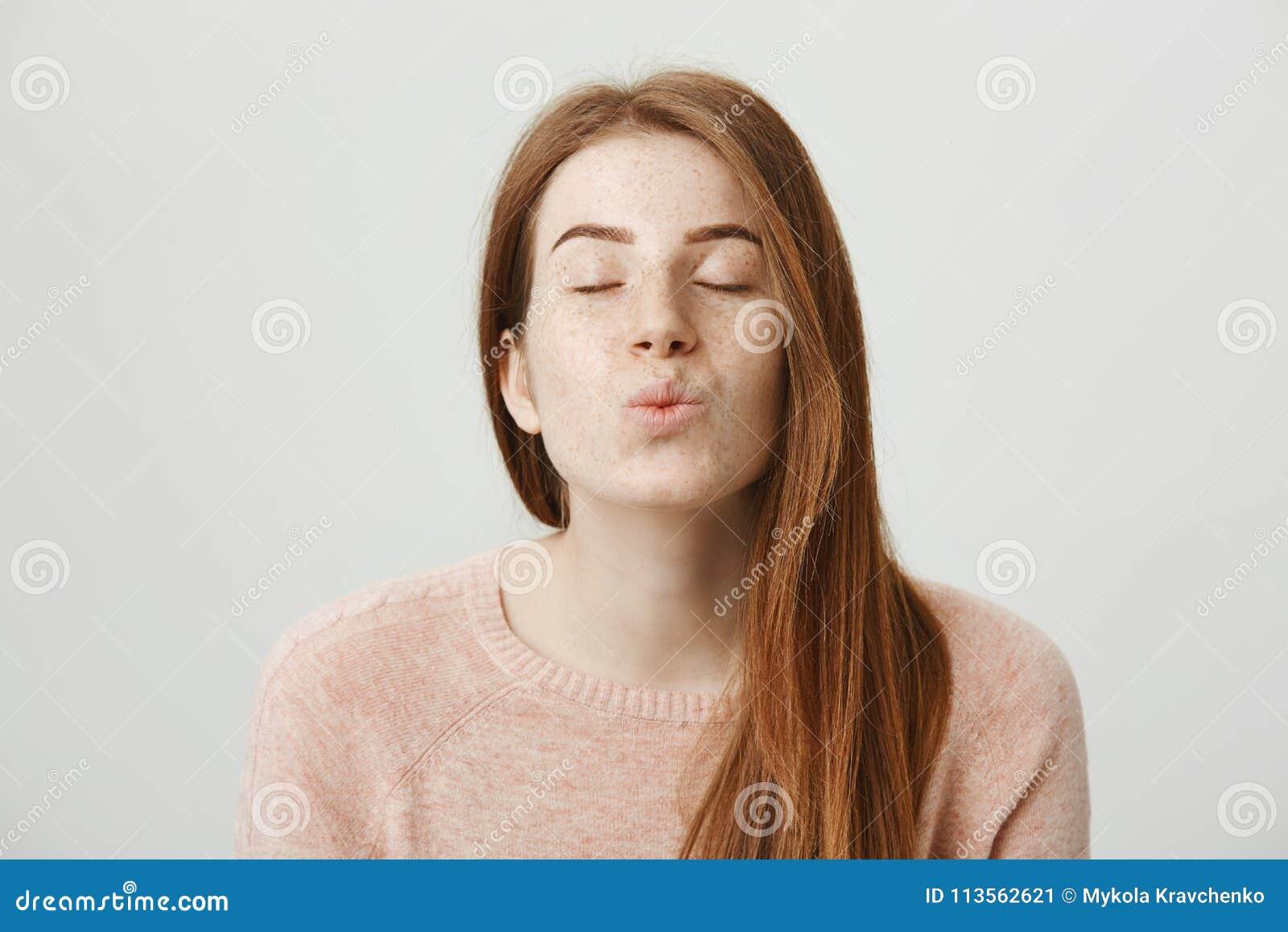 Портрет конца-вверх милой и нежной женщины redhead стоя с закрытыми глазами и довольным выражением, складывая губами и