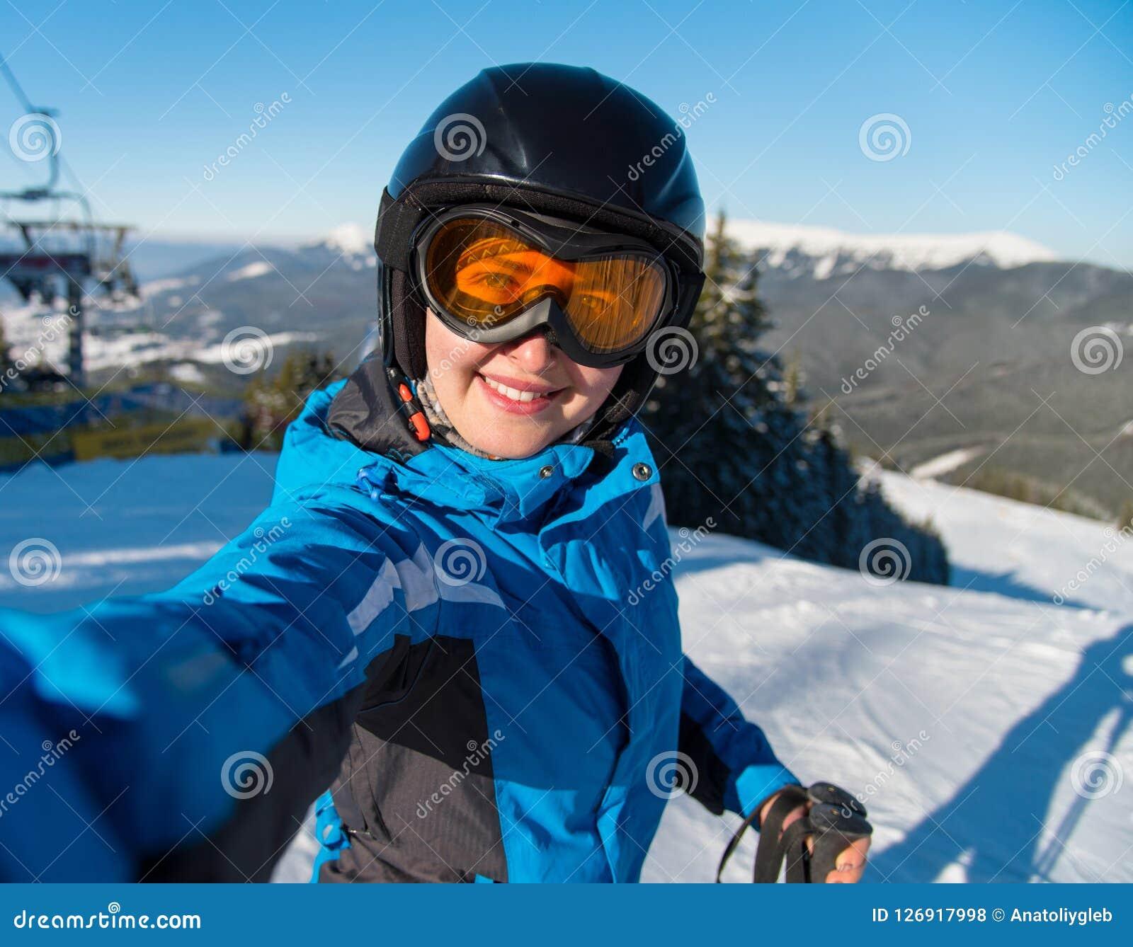 Портрет конца-вверх счастливого лыжника женщины усмехаясь, принимая selfie пока отдыхающ на наклоне после кататься на лыжах