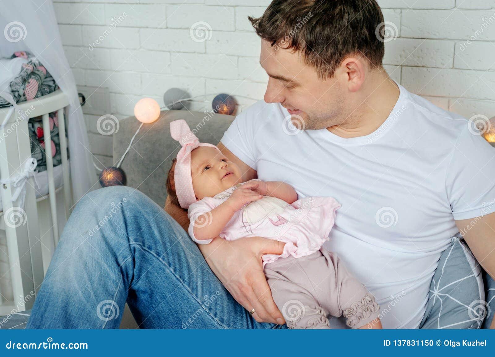 Портрет конца-вверх счастливого молодого отца обнимая и целуя его сладостный прелестный новорожденный ребенка семья принципиально