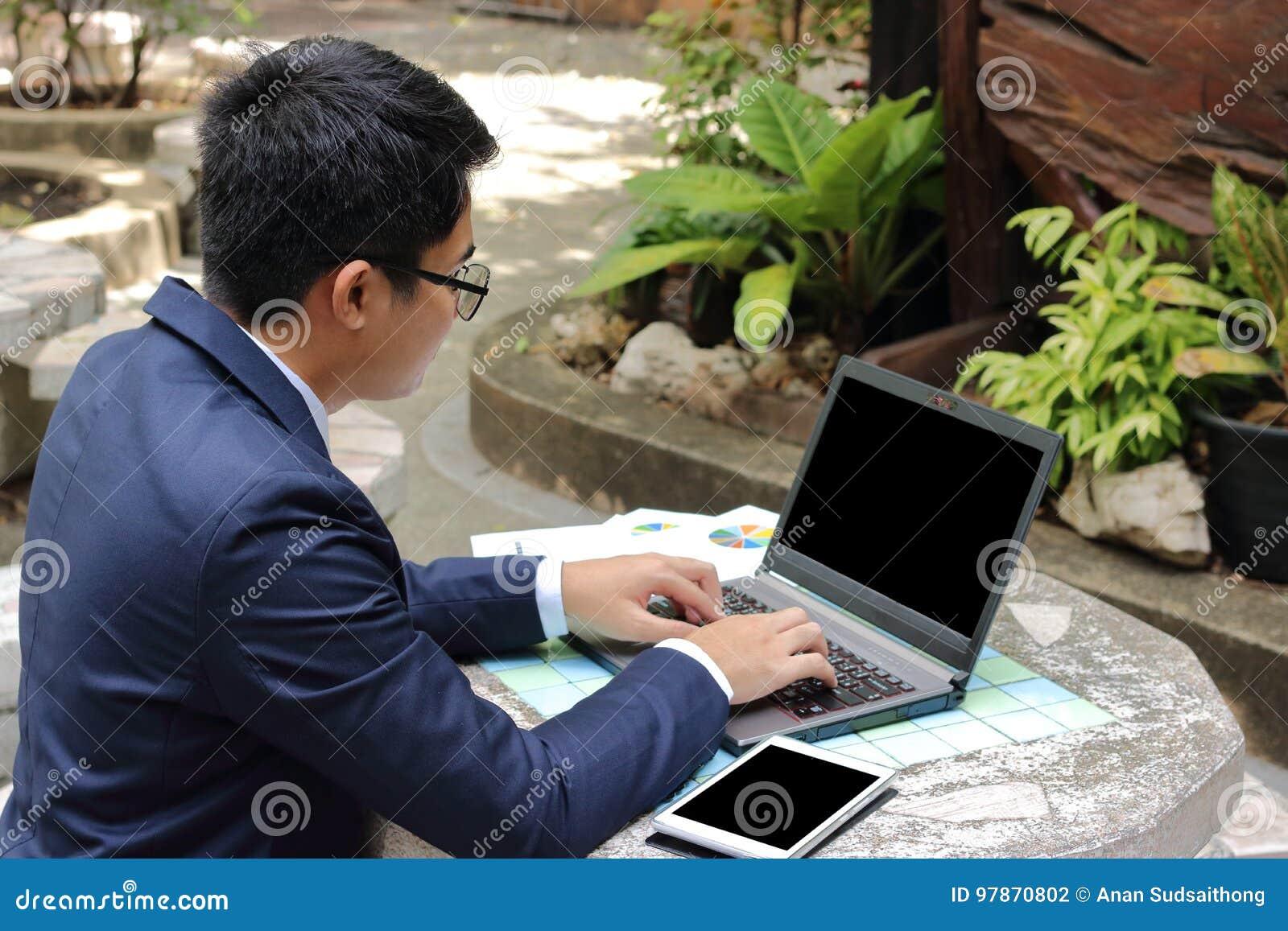 Портрет красивого бизнесмена работая с портативным компьютером outdoors в парке города