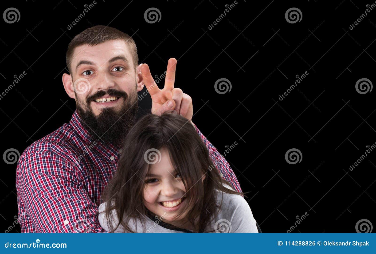Портрет красивого отца и его милой дочери обнимая, looki