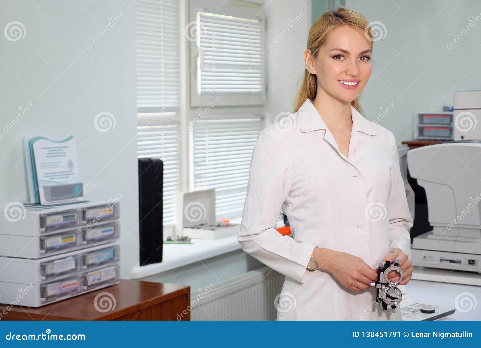 Портрет красивого положения глазного врача с ophthalmologic прибором в шкафе