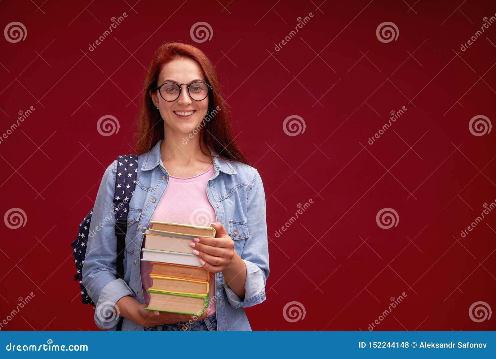 Портрет красивого студента девушки с рюкзаком и стога книг в его руках усмехается на красной предпосылке