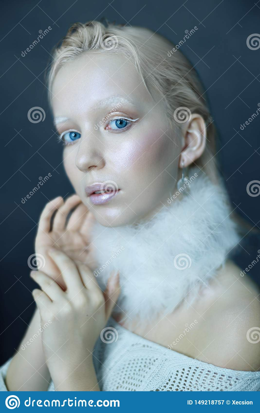 Портрет красивой девушки в заморозке на его стороне на голубой предпосылке льда