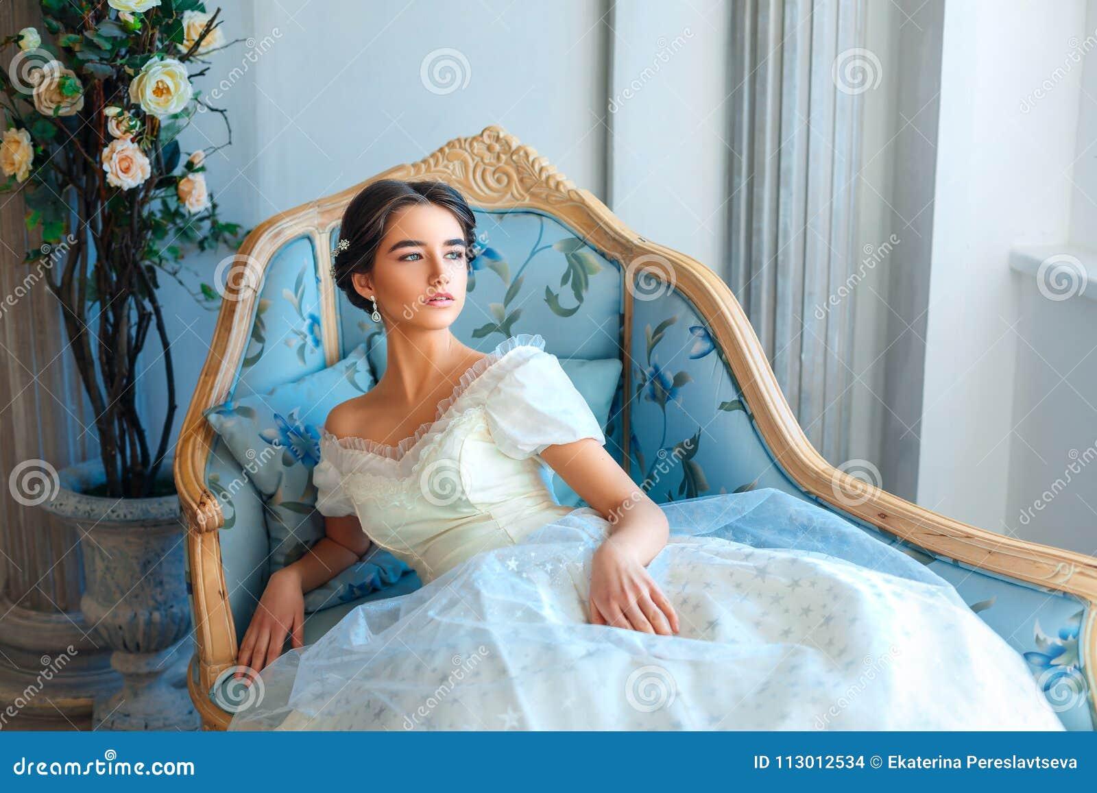 Портрет красивой девушки которая читает книгу на софе в красивом платье