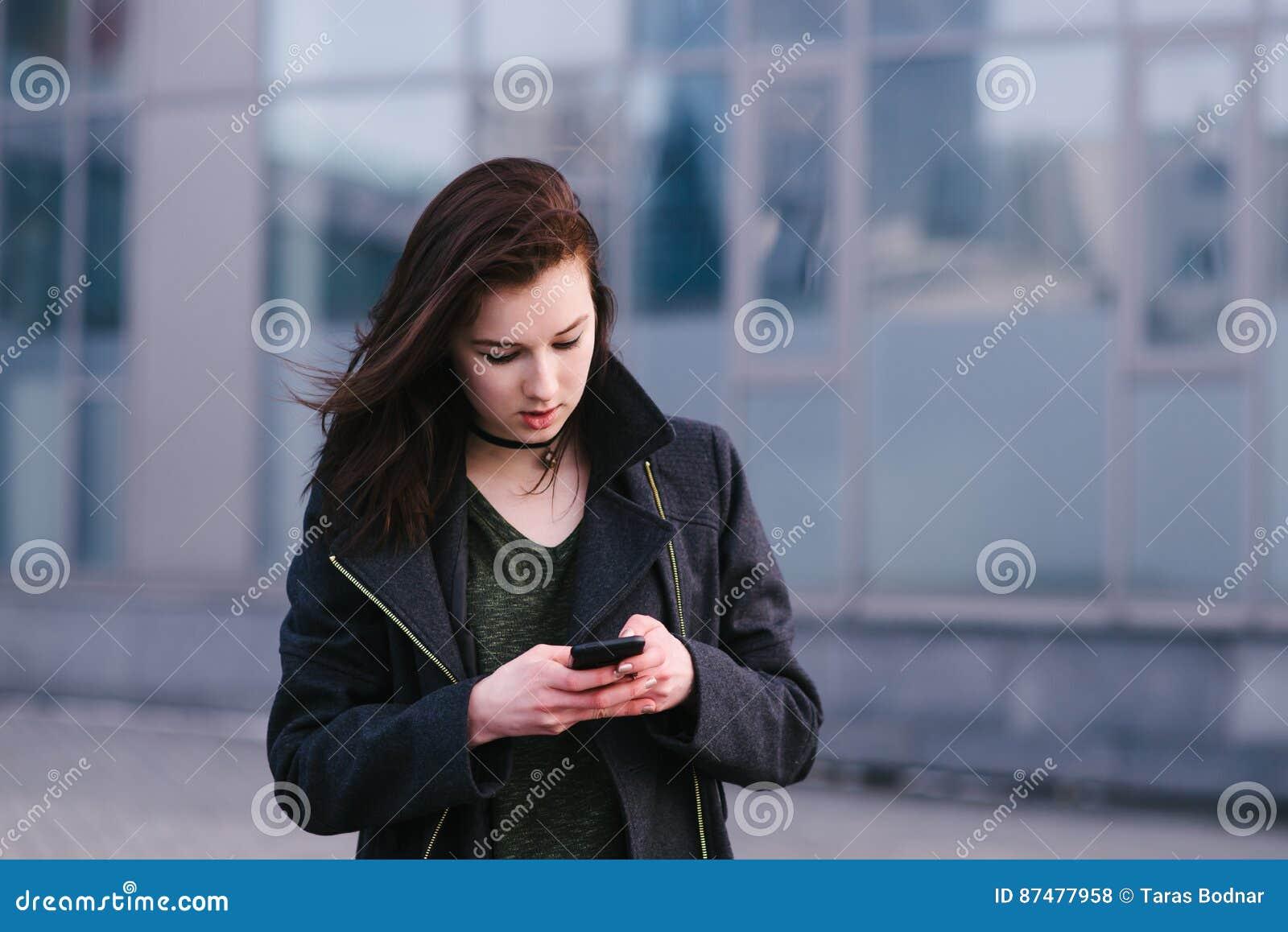 Портрет красивой девушки брюнет одел в черноте, которая использует мобильный телефон на предпосылке современной архитектуры