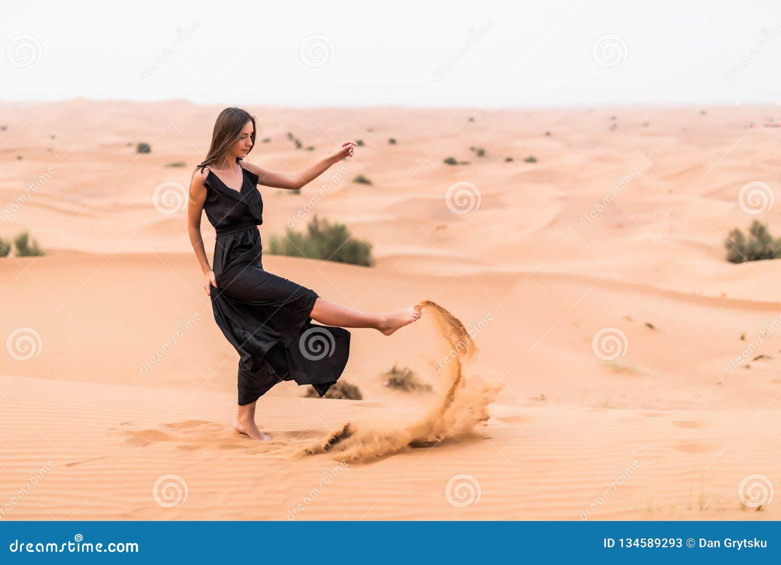 Портрет красивой женщины в длинный порхая черный представлять платья на открытом воздухе на песочной пустыне