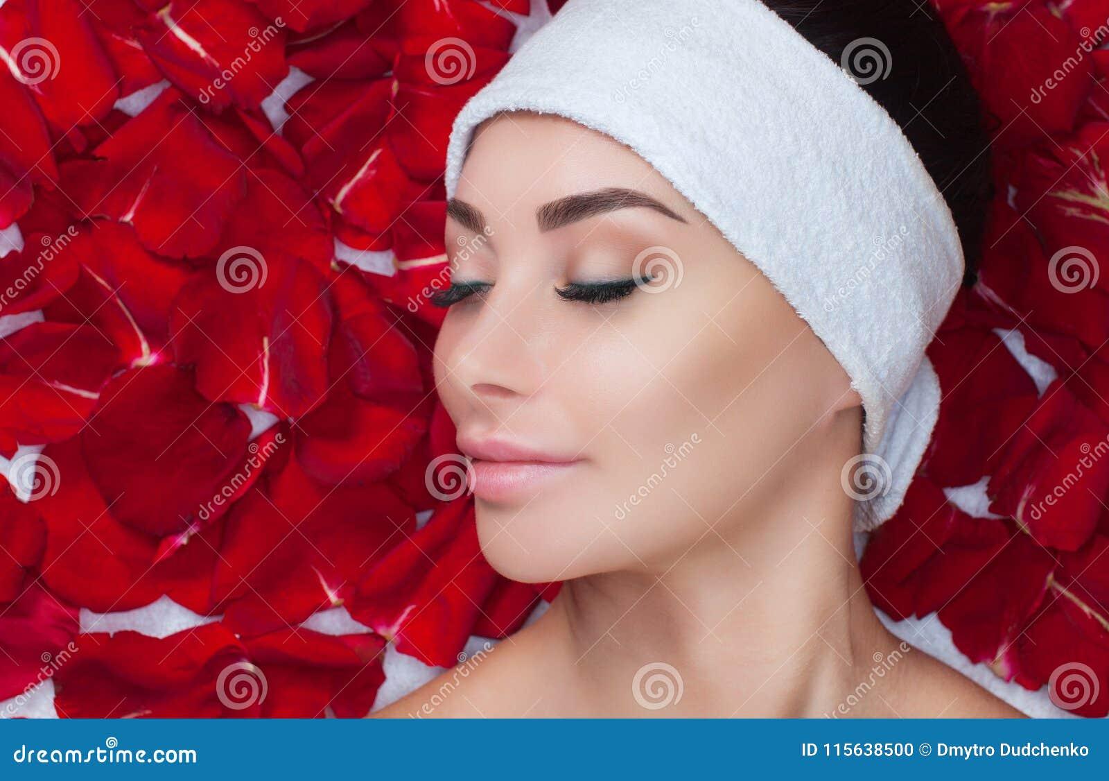 Портрет красивой женщины в салоне курорта перед косметикой на фоне лепестков красной розы