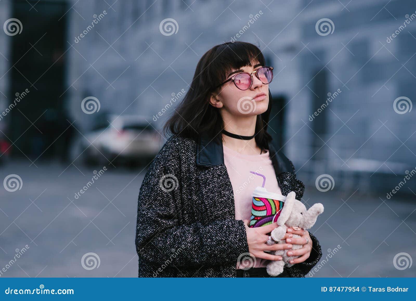Портрет красивой и стильной девушки в стеклах держа кофе и мягкую игрушку на предпосылке города