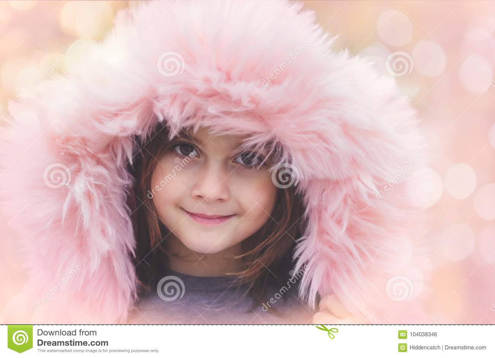 Портрет красивой маленькой девочки с розовым клобуком меха