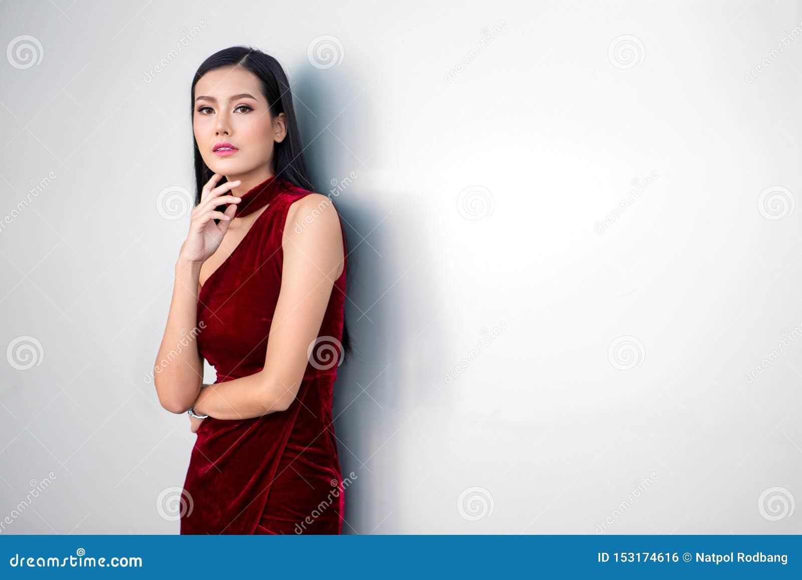Портрет красивой молодой азиатской женщины в красном платье представляя с рукой на подбородке и смотря прочь на белой предпосылке