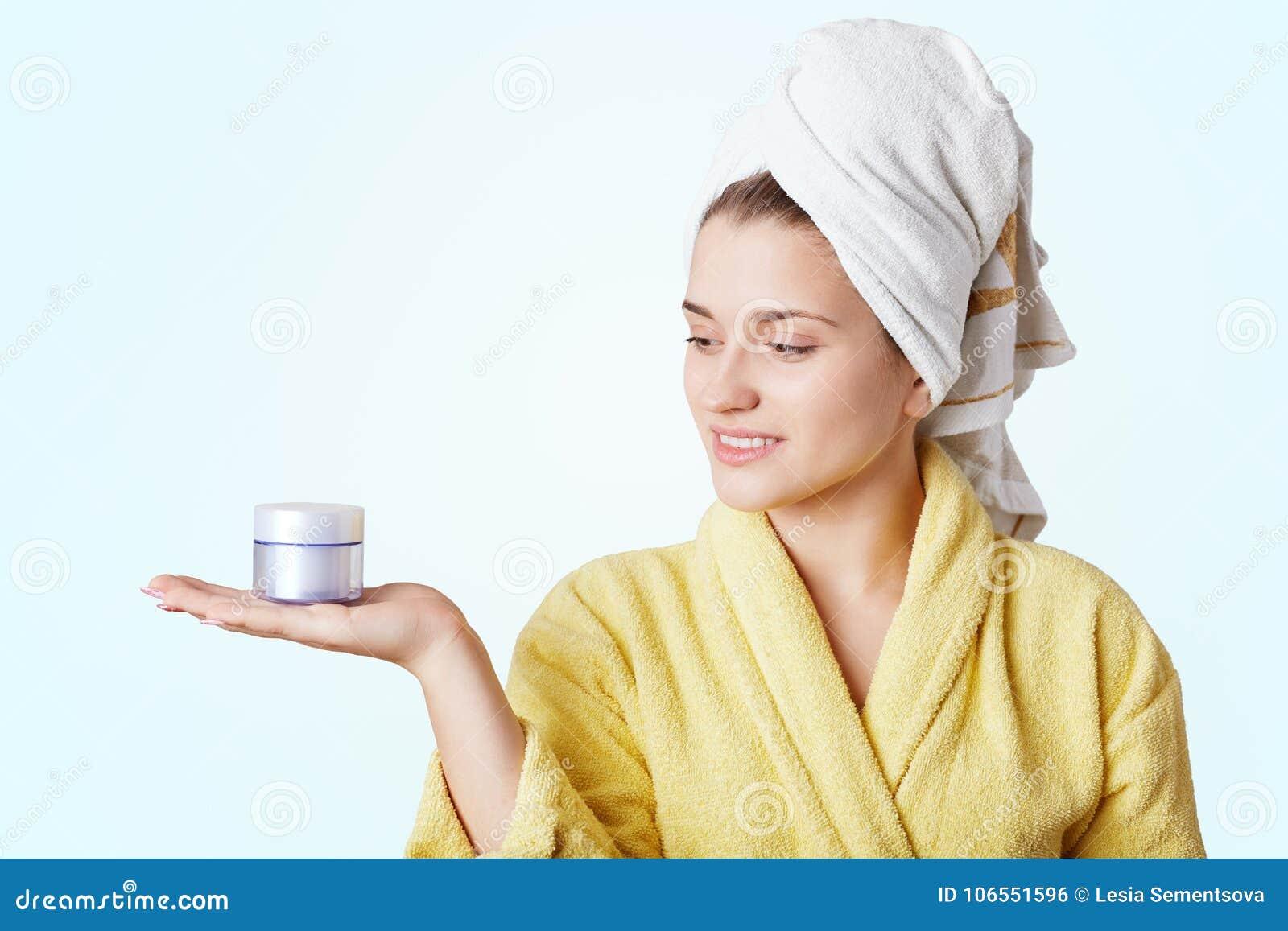 Портрет красивой молодой женщины носит купальный халат и полотенце, держит сливк, идя сделать лицевой щиток гермошлема, белую пре