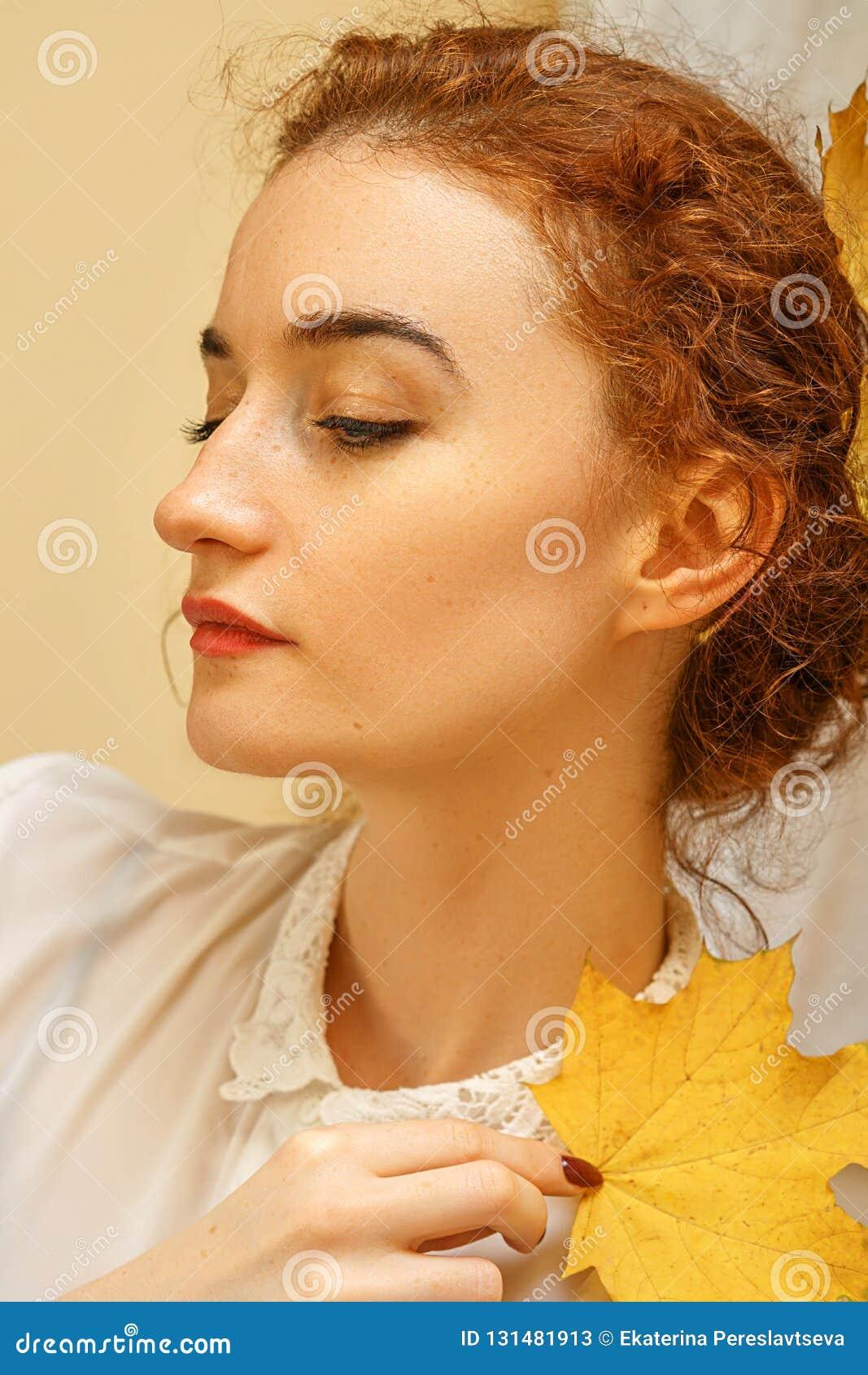 Портрет красивой молодой женщины с красными волосами, усмехаясь со счастьем