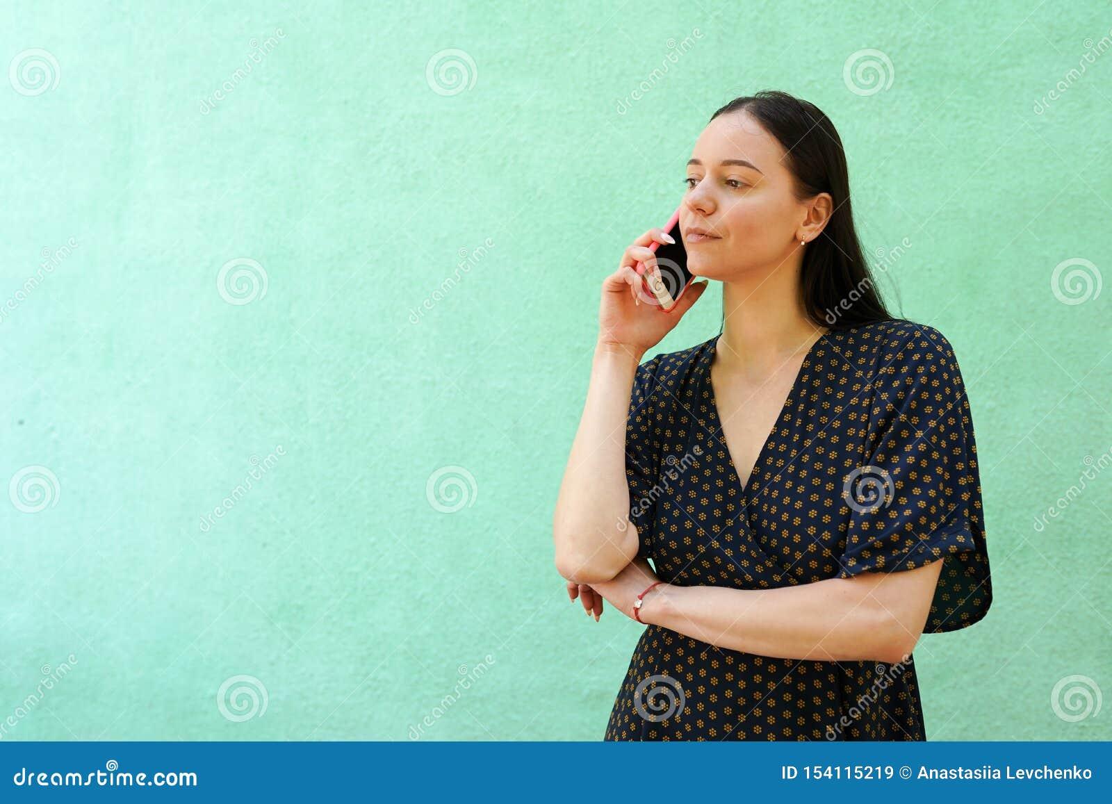 Портрет красивой молодой женщины taltking по телефону на зеленой предпосылке с космосом экземпляра