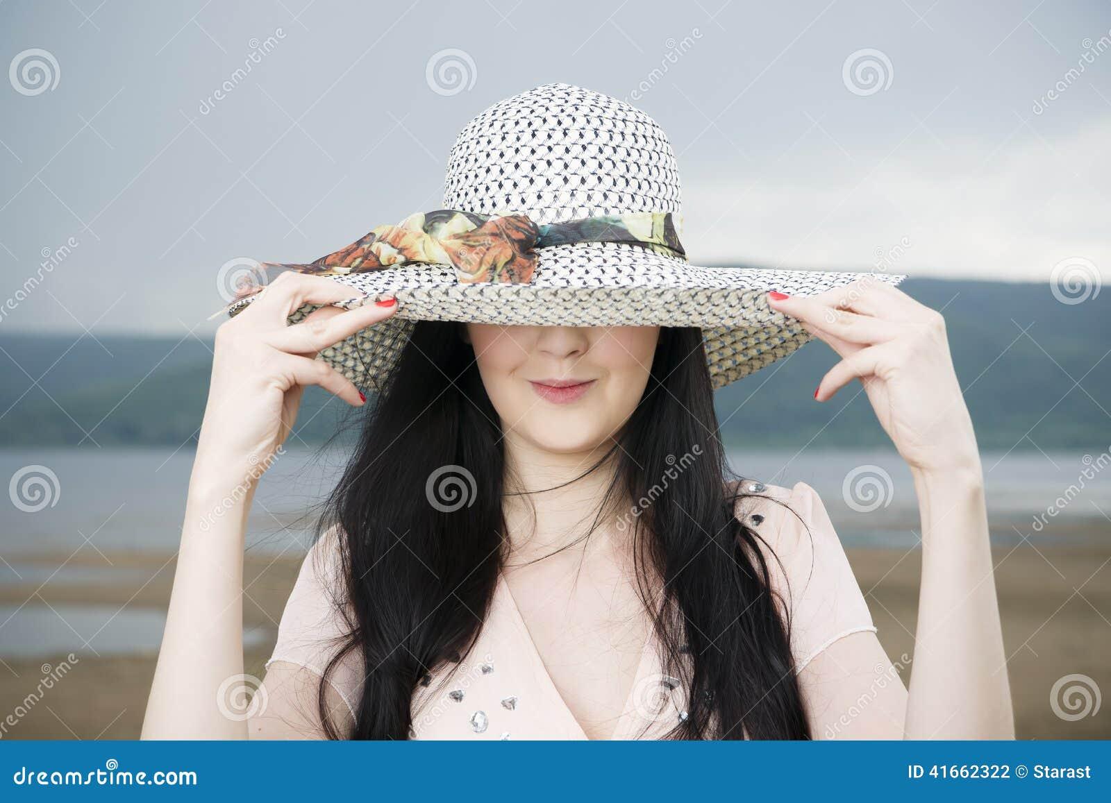 Портрет красивой молодой женщины в шляпе в лете