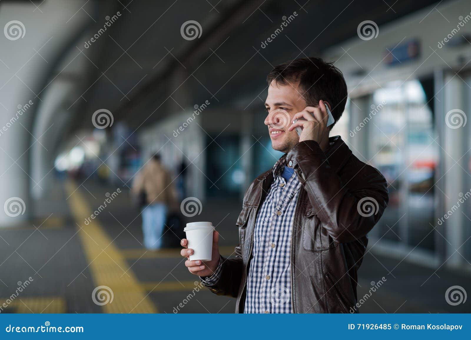 Портрет красивой стойки молодого человека около полета авиапорта ждать следующего и говорить на мобильном телефоне
