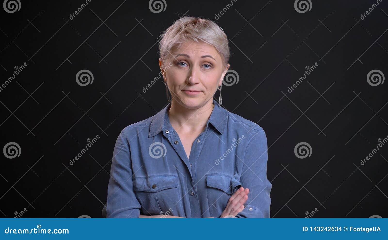 Портрет крупного плана взрослой привлекательной кавказской будучи надоеданным женщины и имеющ ее оружия быть пересеченным над ком