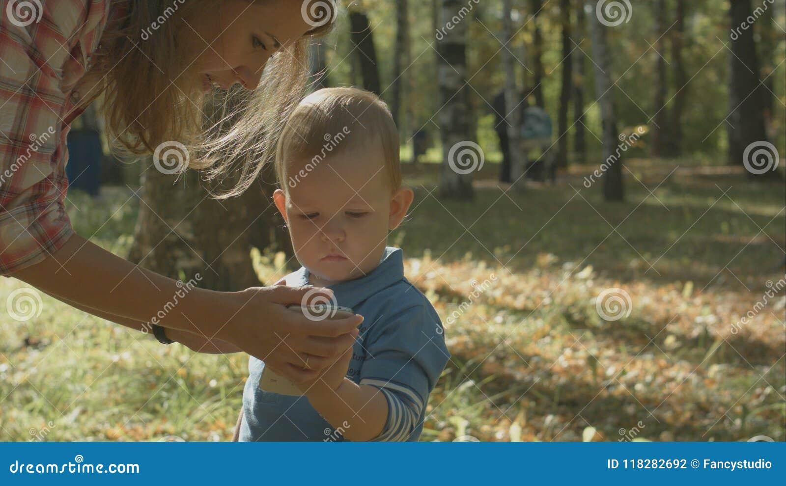 Портрет крупного плана матери наблюдая, как ее сын поговорил на сотовом телефоне