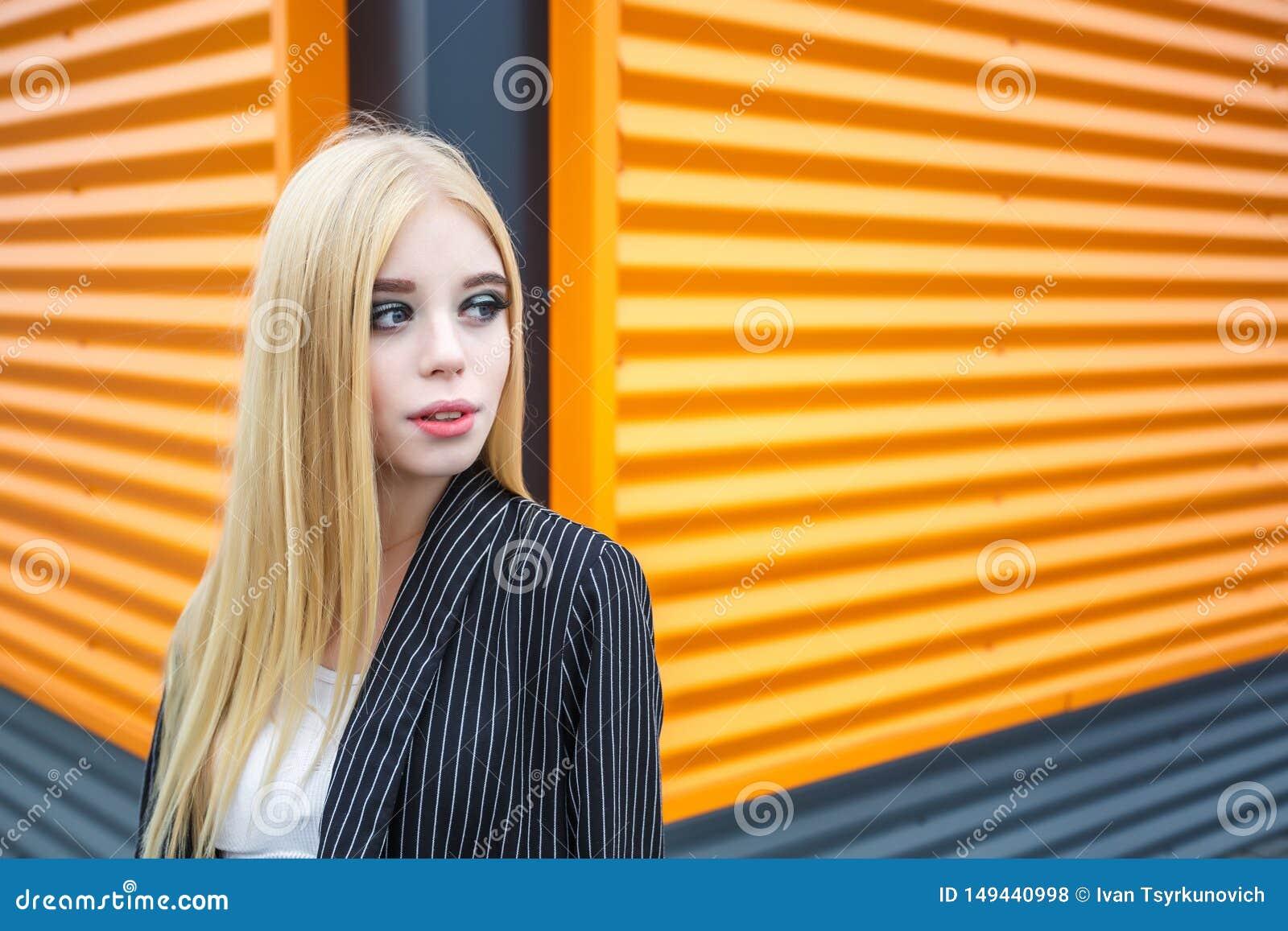 Портрет крупного плана милой усмехаясь маленькой модельной девушки в striped куртке и солнечных очках представляя около серого ри