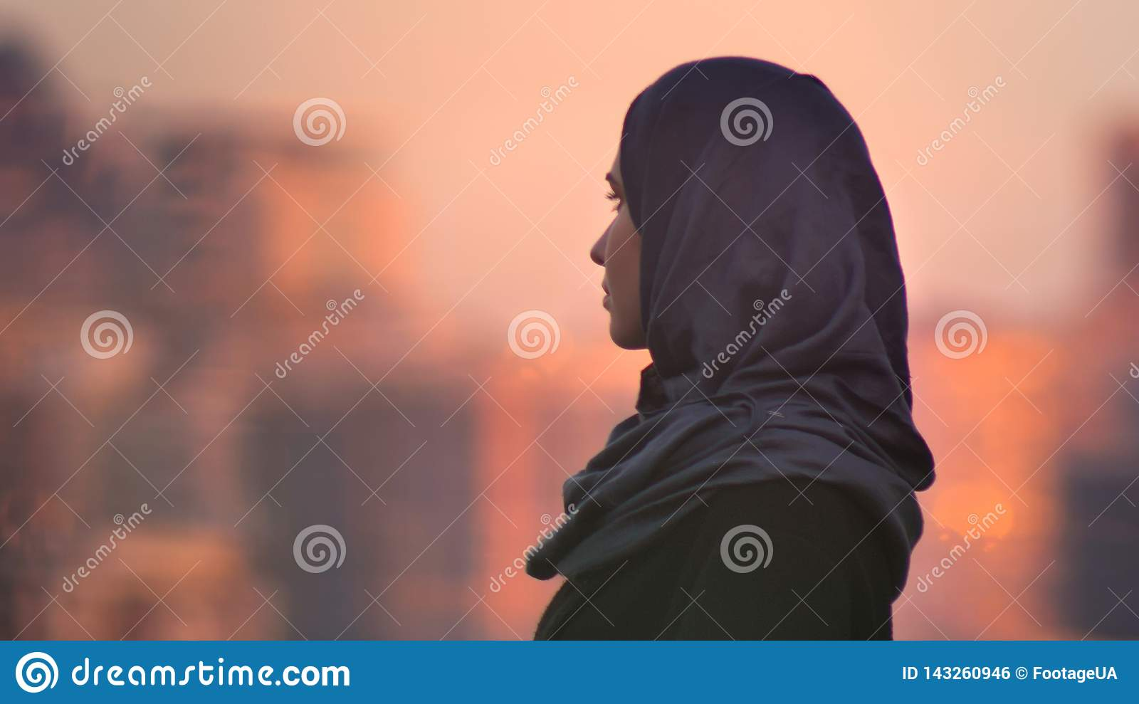 Портрет крупного плана молодой милой женщины в hijab смотря вперед со зданиями городских условий и светить на