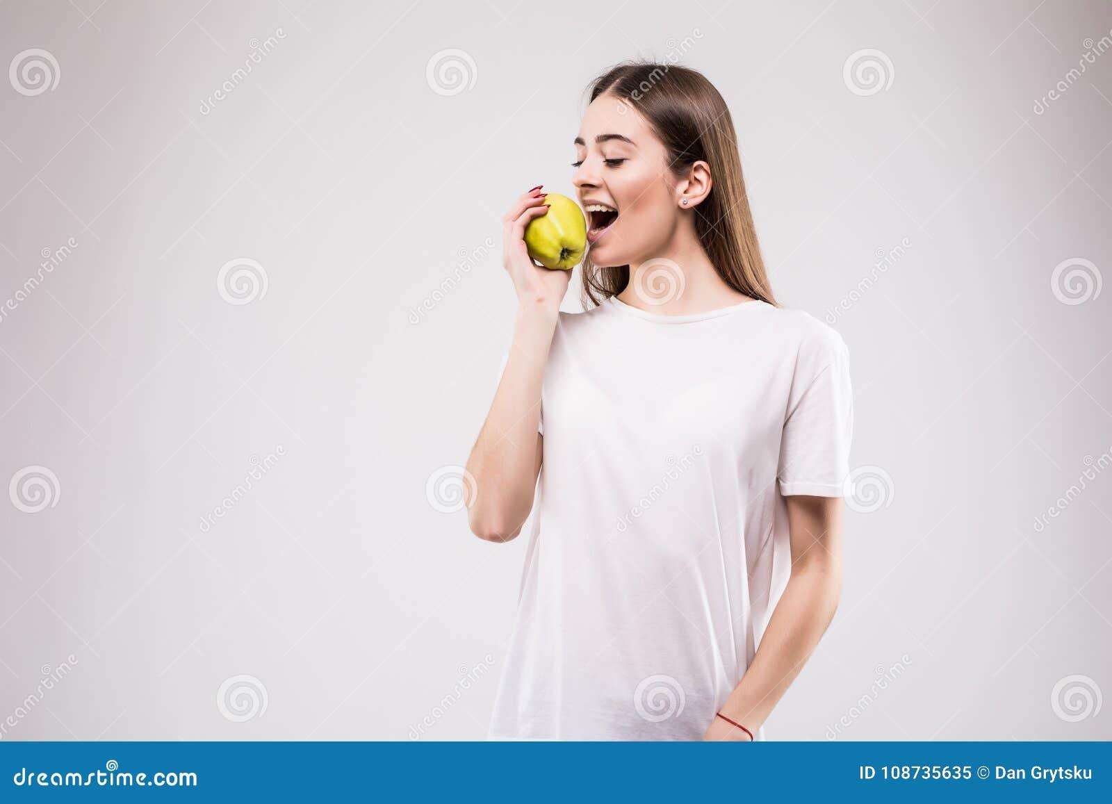 Портрет крупного плана симпатичной молодой женщины брюнет сдерживая сочное свежее очень вкусное яблоко против серой предпосылки К