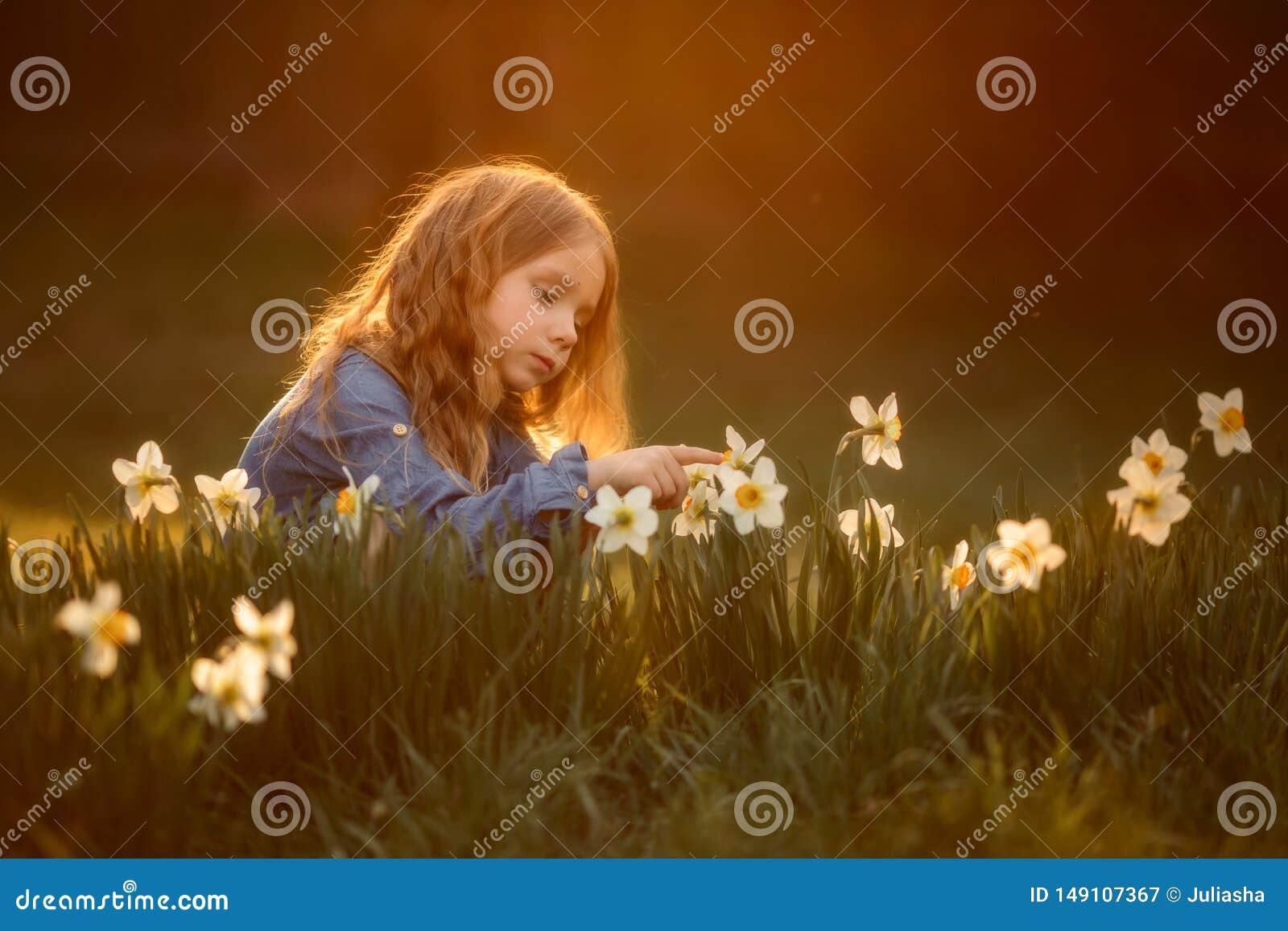 Портрет маленькой девочки на открытом воздухе около цветков narcissus на заходе солнца