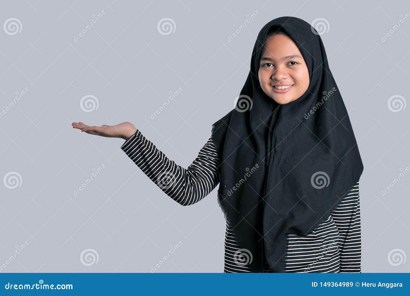 Портрет маленькой девочки нося исламский головной платок показывая пустую зону для знака или copyspase