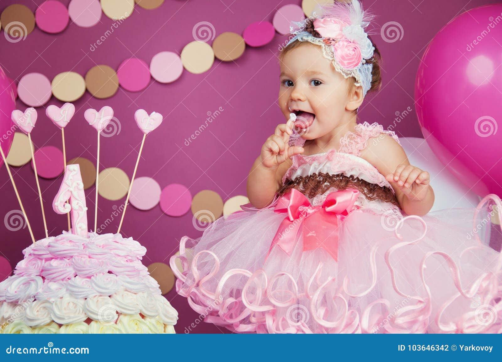 Портрет маленькой жизнерадостной девушки дня рождения с первым тортом Еда первого торта Торт огромного успеха