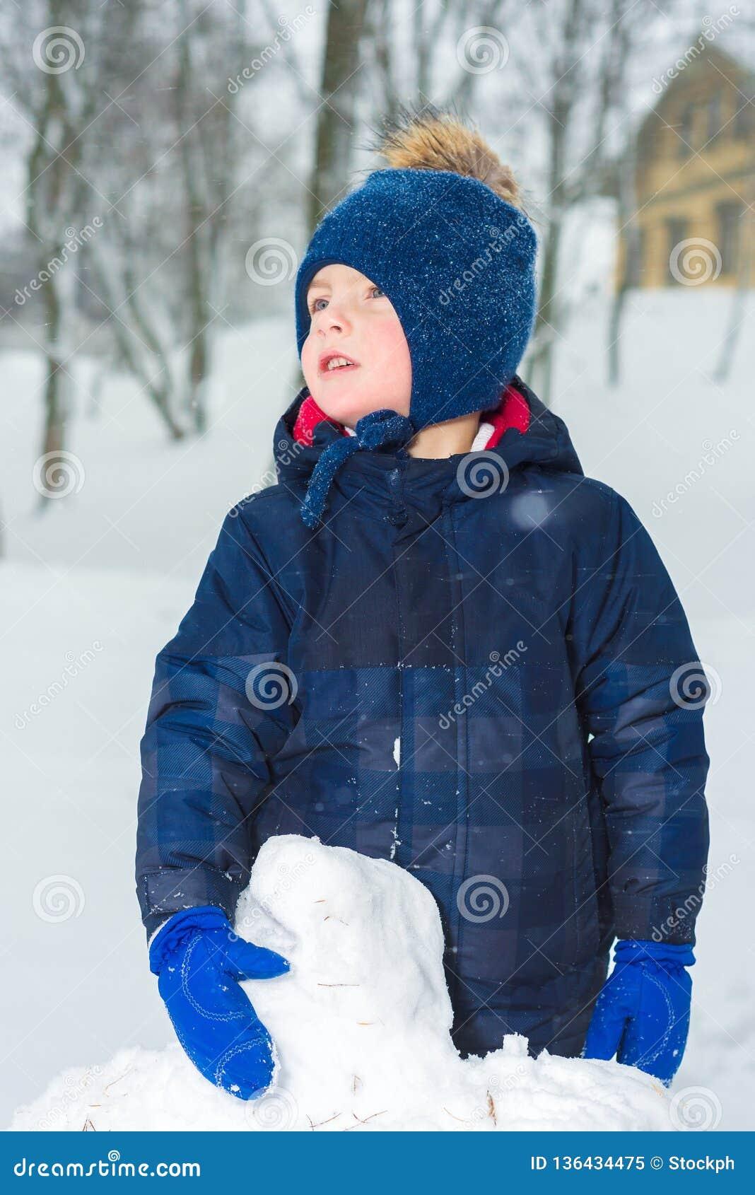 Портрет мальчика в зиме ребенок одет в одеждах шляпе, куртке и mittens зимы