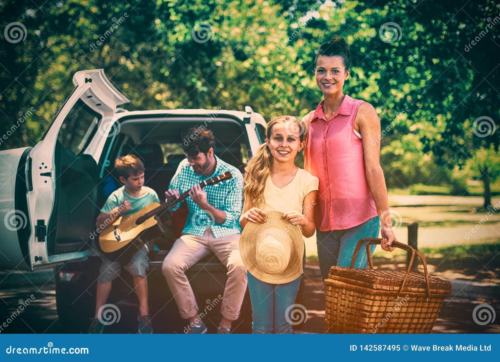 Портрет матери и дочери стоя с корзиной пикника пока отец и сын играя гитару в b