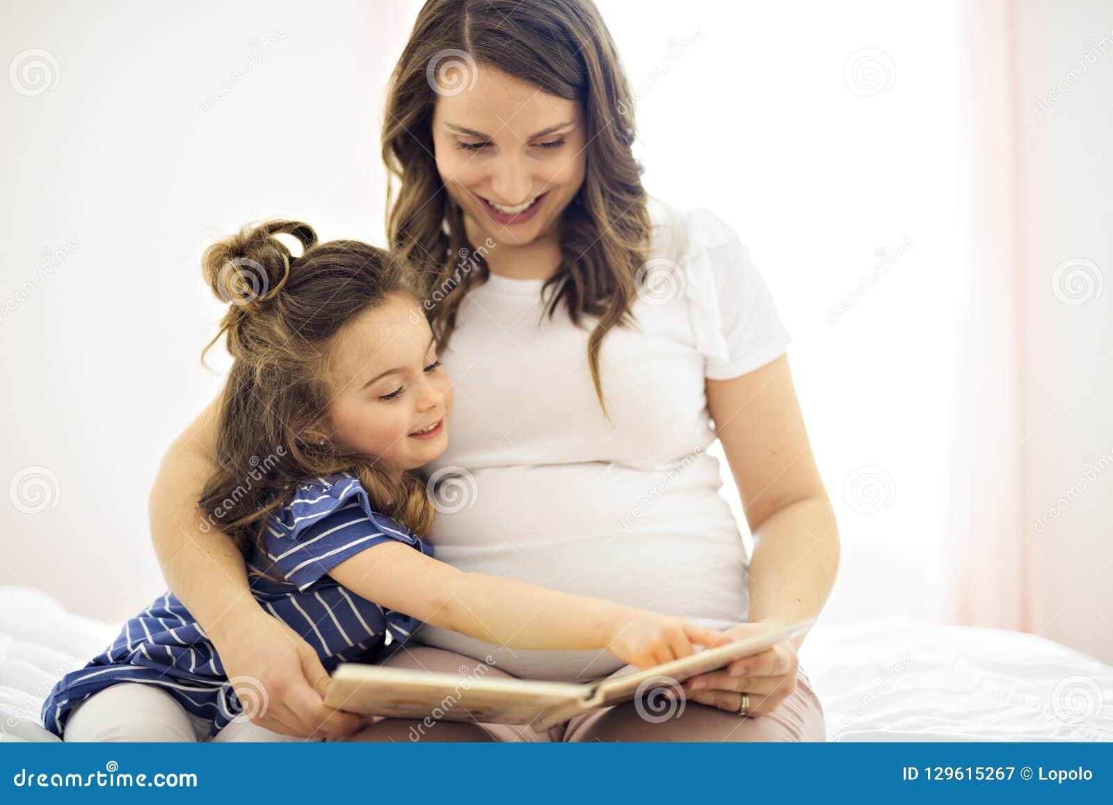 Портрет матери и дочери читая книгу лежа и ослабить в кровати