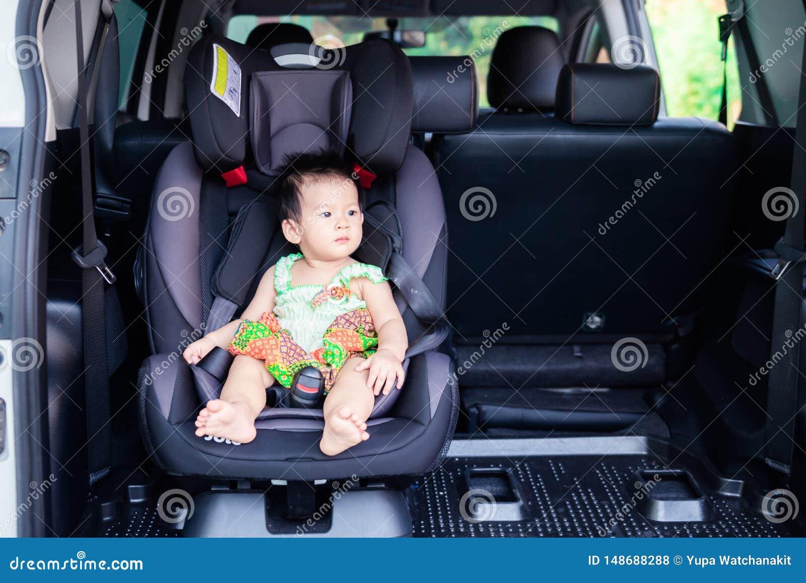 Портрет милого маленького ребенка младенца сидя в автокресле