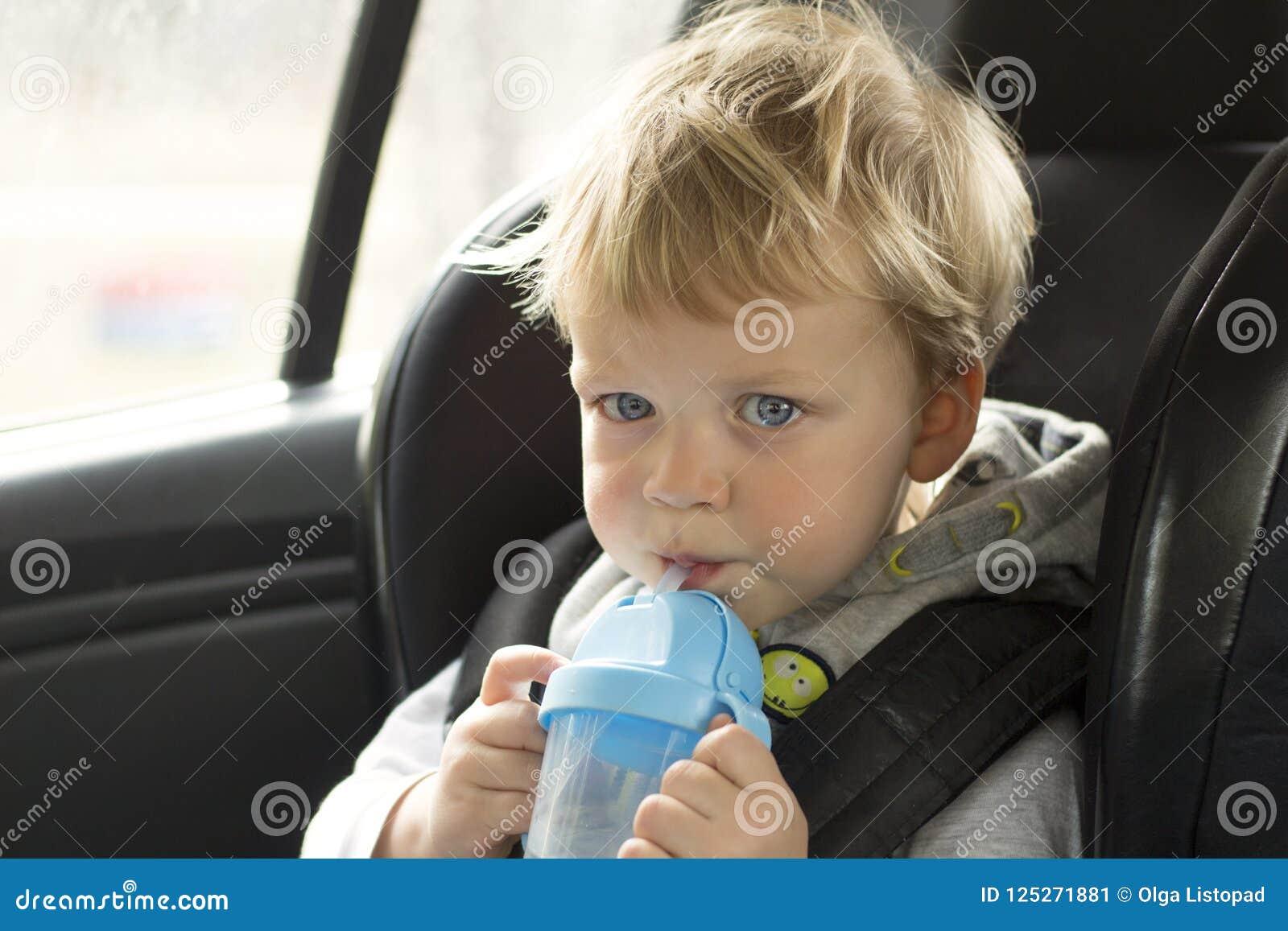 Портрет милого мальчика малыша сидя в автокресле Безопасность транспорта ребенка Прелестный ребёнок с бутылкой с водой
