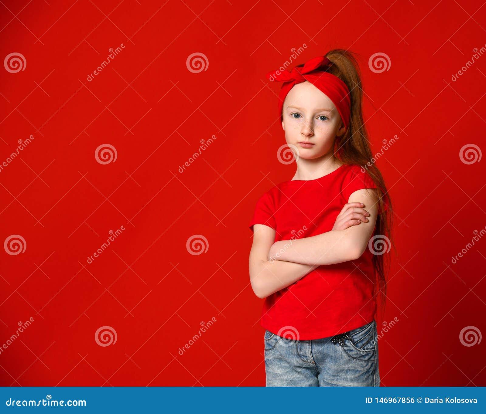 Портрет милой девушки осадил в красном жилете, стоя со сложенными руками и смотря камеру