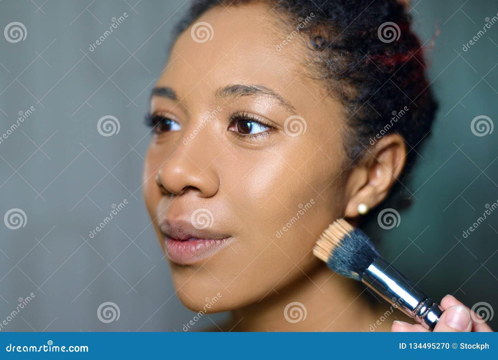Портрет милой девушки с красивым макияжем мастер делает выражение лица с щеткой