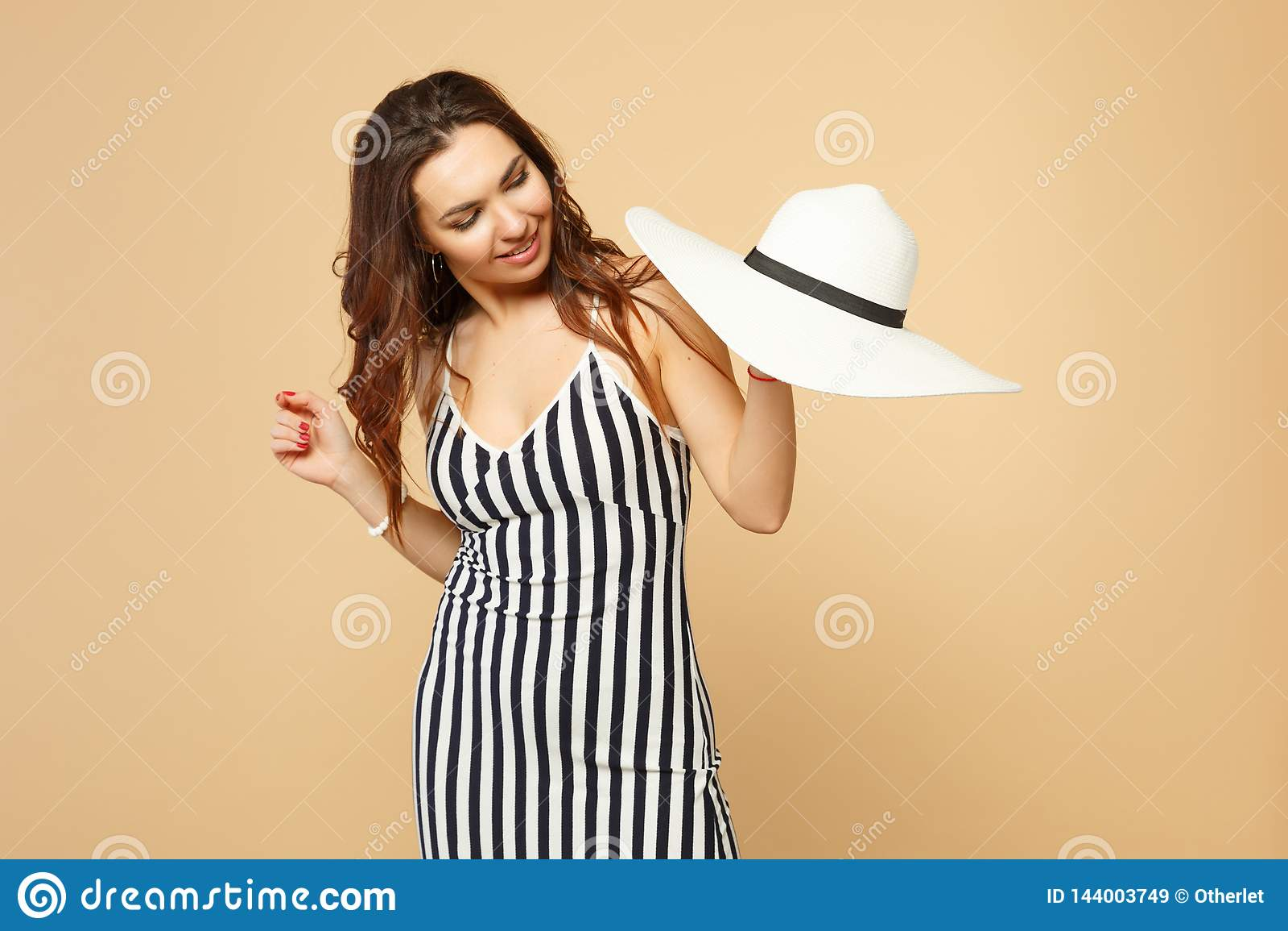 Портрет милой молодой женщины в черно-белом striped платье держа в руке, смотря на шляпе изолированной на пастельном беже