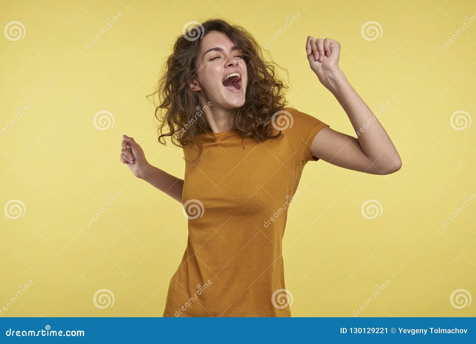 Портрет милой молодой женщины с танцами и петь вьющиеся волосы изолированными над желтой предпосылкой