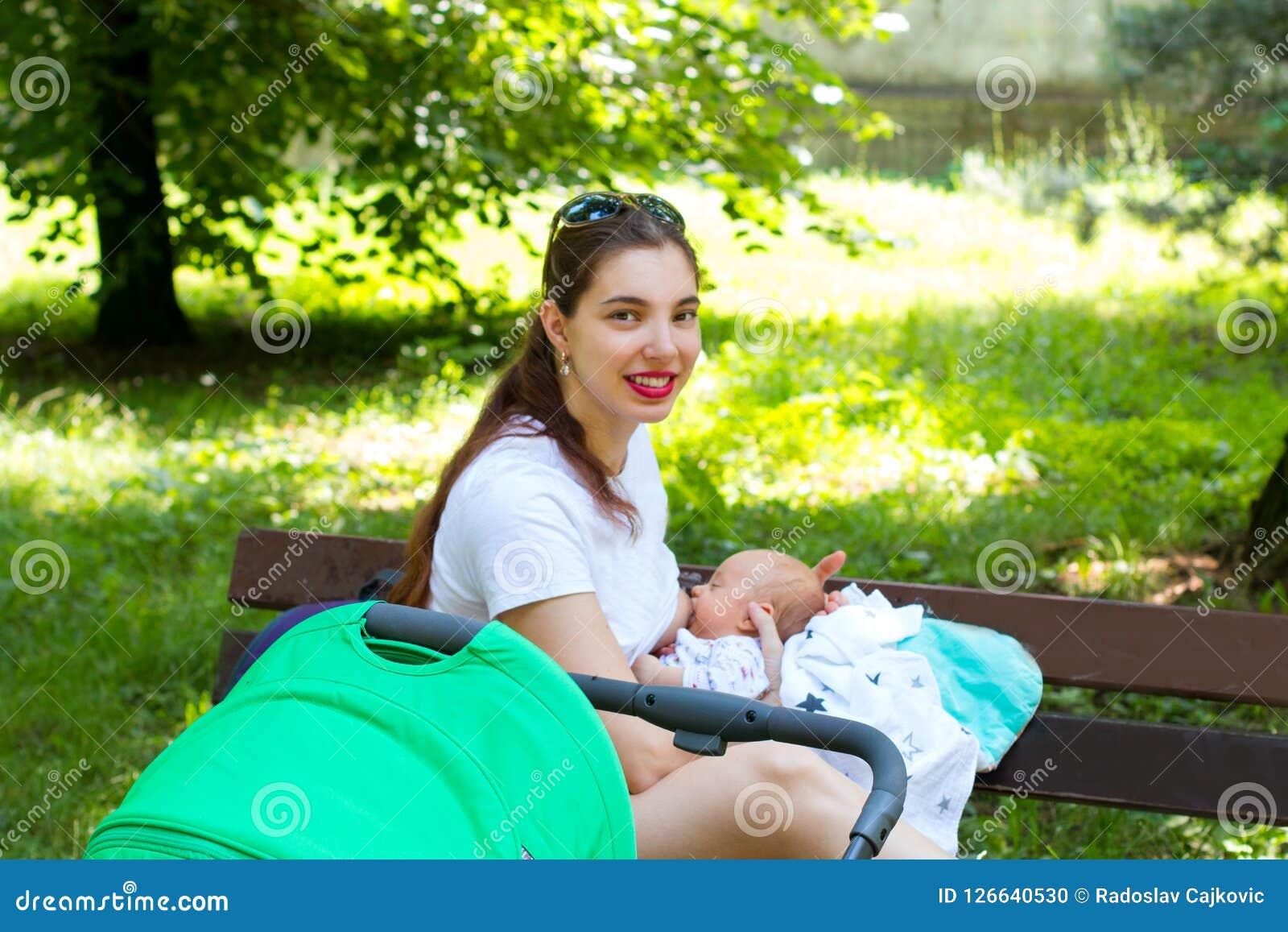 Портрет милых кормящей матери и младенца, молодая мама снаружи при ее новорожденный ребенок для прогулки прогулочной коляски, кор