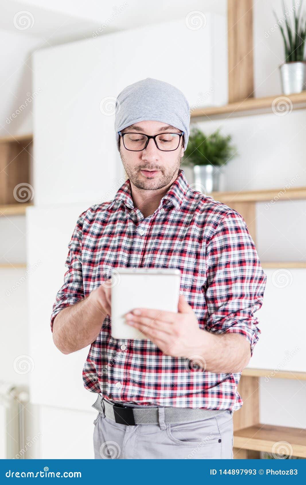 Портрет молодого бизнесмена держа цифровой планшет на современном офисе